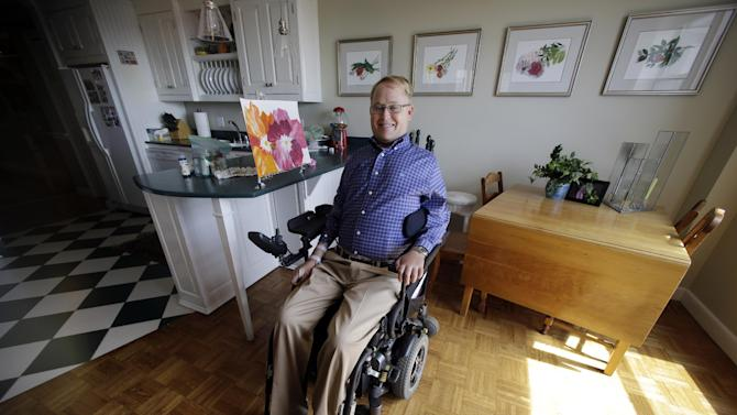In this photo taken Thursday, April 15, 2015, Travis Roy poses in his apartment in downtown Boston. Roy grew into a hockey standout in his first 20 years. He turned 40 on Friday, April 17, and has spent almost half his life in a wheelchair as a paraplegic after slamming into the boards 11 seconds into his first shift for national champion Boston University. He's regained little movement since then but has helped and inspired others with his motivational speaking and foundation that provides equipment for victims of paralysis. (AP Photo/Elise Amendola)