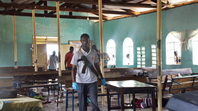 An armed Kenyan policeman walks inside the African Inland Church, as a body of one of those killed in the attack lies on the ground underneath church pews, in Garissa, Kenya, on Sunday, July 1, 2012. Grenade and gunfire attacks on two Kenyan churches near the border with Somalia killed 10 people and wounded 40 on Sunday in what was likely an attack by militants from Somalia, an official said. (AP Photo/Chris Mann)
