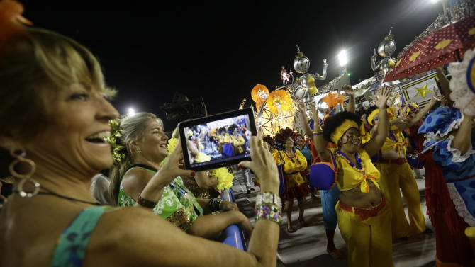 A woman takes photos of performers from the Sao Clemente samba school during carnival celebrations at the Sambadrome in Rio de Janeiro, Brazil, Monday, Feb. 11, 2013. (AP Photo/Silvia Izquierdo)