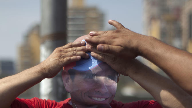 A supporter of ruling party presidential candidate Nicolas Maduro pokes fun at opposition candidate Henrique Capriles by putting on a mask in Capriles' likeness, as supporters wait to move to the site of Maduro's closing campaign rally in Caracas, Venezuela, Thursday, April 11, 2013. Maduro,  Chavez's hand-picked successor, is running against opposition candidate Henrique Capriles in the upcoming April 14 presidential election. (AP Photo/Ramon Espinosa)