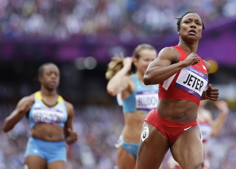 United States' Carmelita Jeter, right, crosses the finish line in a women's 100-meter heat during the athletics in the Olympic Stadium at the 2012 Summer Olympics, London, Friday, Aug. 3, 2012. (AP Photo/Anja Niedringhaus)