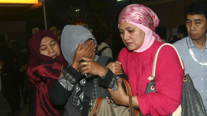 A relative weeps after inspecting the list of passengers reportedly on board a missing Russian airplane at Halim Perdanakusuma Airport  in Jakarta, Indonesia, Wednesday, May 9, 2012. The Russian-made Sukhoi Superjet-100 carrying 46 people lost contact with air controllers while flying over mountains during a demonstration flight Wednesday in western Indonesia, officials said. (AP Photo/Tatan Syuflana)