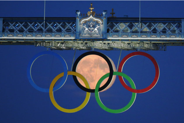 The full moon rises through the Olympic Rings hanging beneath Tower Bridge during the London 2012 Olympic Games