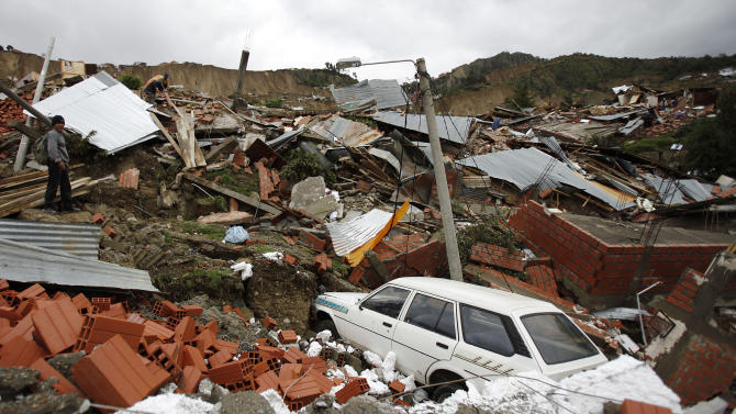 A man stands among debris after a landslide triggered by heavy rain in the Kupini II neighborhood of La Paz, Bolivia, Monday Feb. 28, 2011. Heavy rains caused a hilltop to collapse in a poor neighborhood of the Bolivian capital Sunday, cracking roads, destroying at least 400 homes and burying people's belongings under mud and debris. (AP Photo/Juan Karita)
