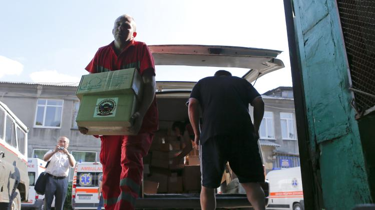 Men unload a van carrying humanitarian medical supplies for a first-aid station in the settlement of Makiivka
