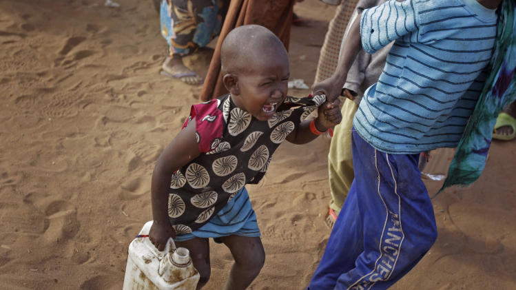 A child cries out as his brother pulls him after they were handed food at a World Food Programme, WFP,  compound in a displacement camp in Dadaab, Kenya, Sunday, July 31, 2011. Dadaab, a camp designed for 90,000 people now houses around 440,000 refugees. Almost all are from war-ravaged Somalia. Some have been here for more than 20 years, when the country first collapsed into anarchy. But now more than 1,000 are arriving daily, fleeing fighting or hunger.(AP Photo/Schalk van Zuydam)