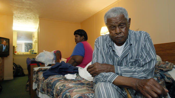 In this May 19, 2011 photograph, Rev. Eddie Walls Jr., right, speaks about his hopes for returning to a standing home after fleeing the flooding from the Mississippi River with his family, including his daughter Linda Walls, center, and grandson Kevin Walls, not seen, in Port Gibson, Miss. The family is sharing a small motel room on the outskirts of town. (AP Photo/Rogelio V. Solis)