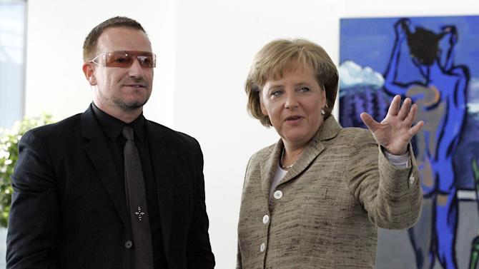 FILE - This is a Tuesday, April 17, 2007 file photo of  German Chancellor Angela Merkel, right, and Bono, left, singer of Irish rock band U2, talk during Bono's visit to the Berlin Chancellery .  (AP Photo/Fritz Reiss, File)