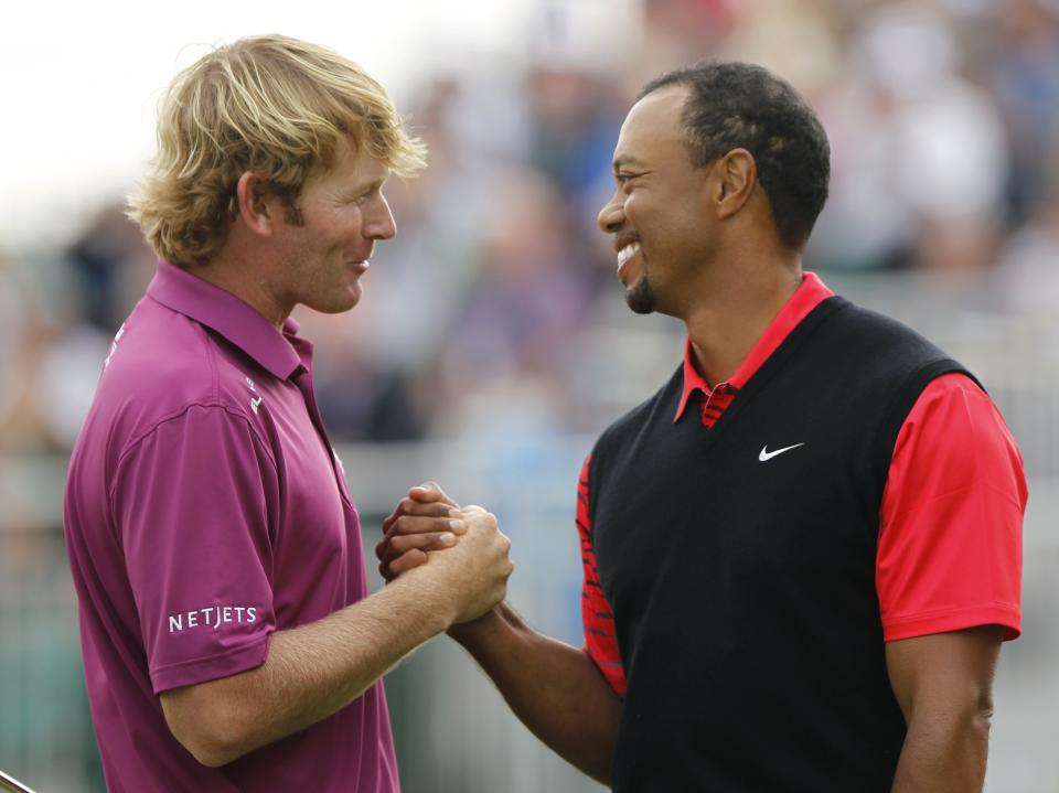 Tiger Woods of the United States shakes hands with Brandt Snedeker of the United States, left, on the 18th green at Royal Lytham & St Annes golf club after their final round of the British Open Golf Championship, Lytham St Annes, England Sunday, July  22, 2012. (AP Photo/Peter Morrison)