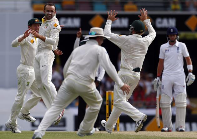 Australia's Lyon celebrates with Bailey after he took the wicket of England's captain Cook during the fourth day's play of the first Ashes cricket test match in Brisbane