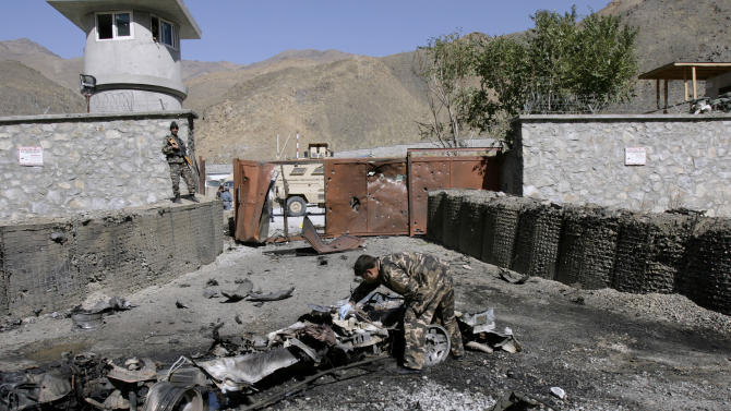 An Afghan security officer, center, collects evidence from the site of an attack by militants at the gate of an American base in Panjshir north of Kabul, Afghanistan, Saturday, Oct. 15, 2011. Militants tried to blast their way into an American base in eastern Afghanistan on Saturday, striking before dawn with rocket-propelled grenades and a vehicle packed with explosives. All four of the attackers were killed and two Afghan security guards were wounded. (AP Photo/Ahmad Jamshid)