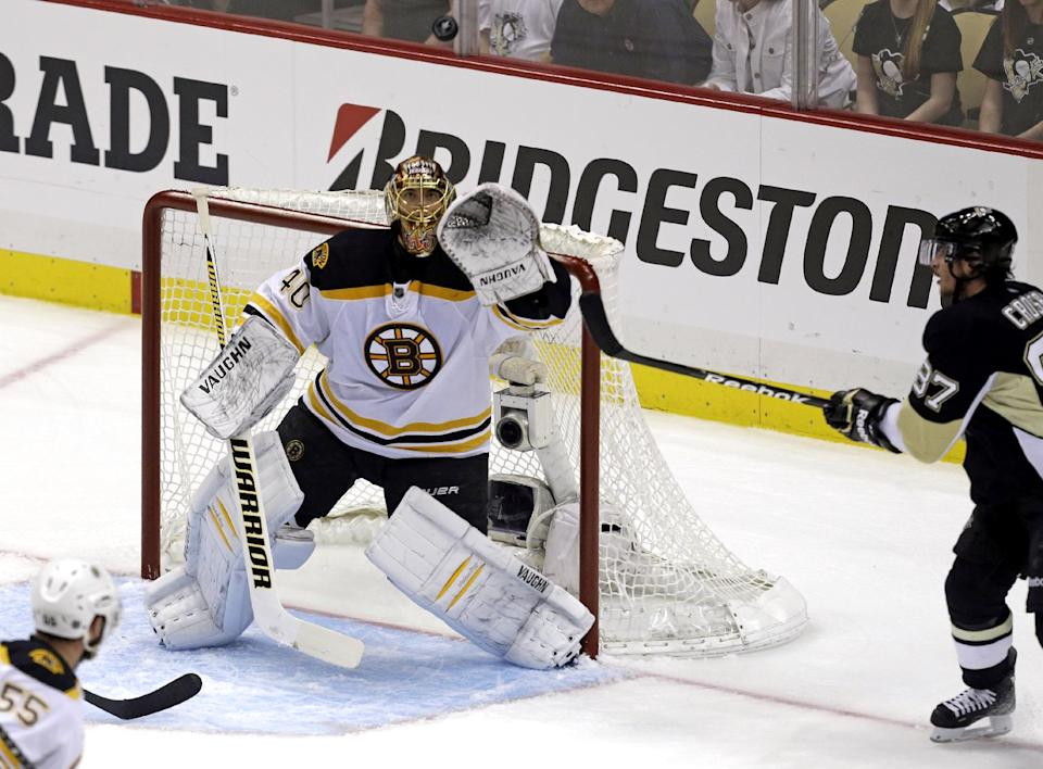 Pittsburgh Penguins' Sidney Crosby (87) and Boston Bruins goalie Tuukka Rask (40) eye the rebounding puck during the first period of Game 1 in an NHL hockey Stanley Cup Eastern Conference finals in Pittsburgh, Saturday, June 1, 2013. (AP Photo/Gene J. Puskar)