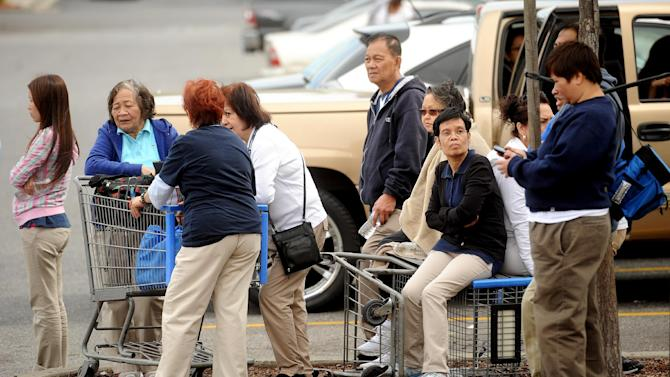 Walmart workers gather outside a Walmart in San Jose, Calif., after a motorist drove through a store entrance and began assaulting shoppers on Sunday, March 31, 2013. Four people sustained injuries during the attack according to a police spokesman. (AP Photo/Noah Berger)