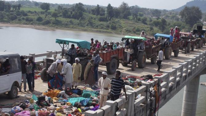 Indian villagers on tractors move past bodies of victims of a stampede on a bridge across the Sindh River in Datia district in Madhya Pradesh state, India, Sunday, Oct. 13, 2013. At least 64 people were killed Sunday in a stampede by masses of Hindu worshippers crossing the bridge to the remote Ratangarh village temple to honor the Hindu mother goddess Durga on the last day of the popular 10-day Navaratra festival. The chaos broke out as rumors spread that the bridge was collapsing, according to D.K. Arya, deputy inspector general of police in the region.(AP Photo)