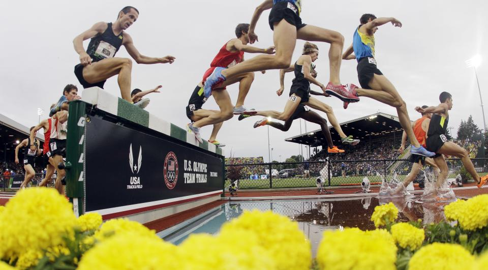 Competitors take the water jump in the men's 3000 meter steeplechase final at the U.S. Olympic Track and Field Trials Thursday, June 28, 2012, in Eugene, Ore. Evan Jager, wearing 13 on his leg, won the race.  (AP Photo/Charlie Riedel)