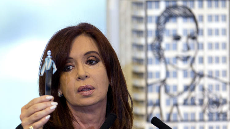 Argentina's President Cristina Fernandez holds up a tube with a sample of the first oil extracted in the country, during her announcement of a bill to nationalize Spain's controlled oil company YPF, at Government House in Buenos Aires, Argentina, Monday April 16, 2012. Fernandez said in an address to the country that the measure sent to congress on Monday is aimed at recovering the nation's sovereignty over its hydrocarbon resources. Behind Fernandez is a scale model of an iron sculpture of Argentina's former first lady and second wife of late President Juan Peron, Eva Peron. (AP Photo/Natacha Pisarenko)
