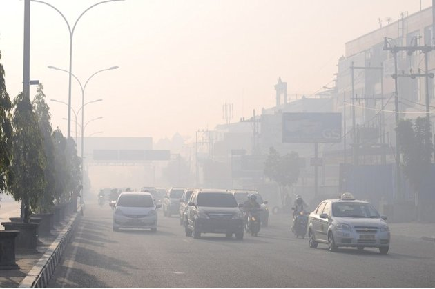 Commuters travel on a road blanketed by haze due to nearby forest fires, in Pekanbaru city, Sumatra on June 19, 2013