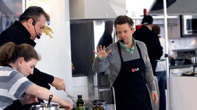 IMAGE DISTRIBUTED FOR LG -  In this photo released on Monday April 8, 2013,   Stephanie Kelly, left, assist Coach Bob Huggins,  of the West Virginia University men's basketball team, as Chef Richard Blais, look on at a head-to-head battle in the kitchen at the LG Coaches' Cook-off during NCAA Final Four weekend in Atlanta.  LG Electronics USA, an official Corporate Partner of the NCAA, hosted the competition and donated $20,000 in the name of Huggins, the winner, to Coaches vs. Cancer, a program that unites the American Cancer Society and the National Association of Basketball Coaches in the fight against cancer. ( Photo by Wilford A Harewood/Invision for LG/AP Images)