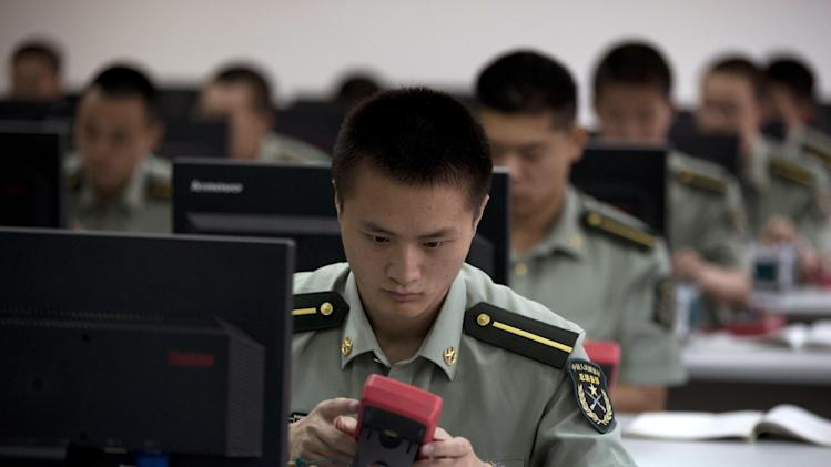 Chinese People's Liberation Army cadets talk part in a digital electronic skills class at the PLA's Armoured Forces Engineering Academy Base, on the outskirt of Beijing, China Tuesday, July 22, 2014. China opened its military academy to local and foreign media Tuesday displaying their weaponry, rolling tanks, bayonet drills and dancing robots at their base. (AP Photo/Andy Wong)