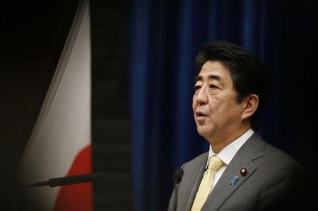 Japan's Prime Minister Shinzo Abe speaks next to the Japanese national flag, attached with a black ribbon to mourn victims during a news conference at his official residence in Tokyo March 10, 201