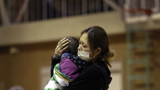 FILE - In this March 16, 2011 file photo, a woman holds her child at a shelter after being evacuated from areas around the Fukushima nuclear facilities damaged by last week's major earthquake and following tsunami in Fukushima city, Fukushima prefecture, Japan. Experts and the government say there have been no visible health effects from the radioactive contamination from Fukushima Dai-ichi so far. But they also warn that even low-dose radiation carries some risk of cancer and other diseases, and exposure should be avoided as much as possible, especially the intake of contaminated food and water. Such risks are several times higher for children and even higher for fetuses, and may not appear for years. Okinawa has welcomed the people from Fukushima and other northeastern prefectures (states) affected by the March 11, 2011, earthquake and tsunami that set off the nuclear disaster. (AP Photo/Wally Santana, File)