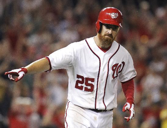 Washington Nationals' Adam LaRoche points at his teammates in the dugout on his way to first base after hitting a game-winning solo home run with two outs in the 11th inning of a baseball game against the Arizona Diamondbacks, Monday, Aug. 18, 2014, in Washington. The Nationals won 5-4 in 11 innings