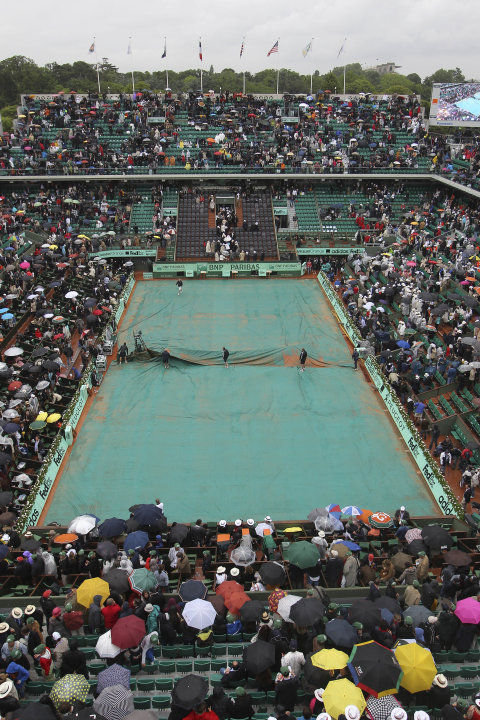 Stadium employees cover center court as the mens final match between Rafael Nadal of Spain and Novak Djokovic of Serbia was suspended because of the rain at the French Open tennis tournament in Roland