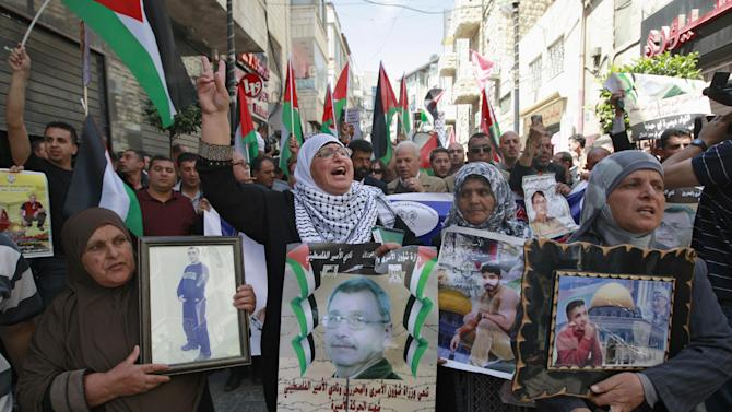 """A Palestinian woman, center,  holds a portrait of Maysara Abu Hamdiyeh, with Arabic that reads, """"the Ministry of Prisoners Affaires and the Palestinian Club of Captivity, mourn the death of captive movement martyr, Brigade Maysara Abu Hamdiyeh, who died because of medical neglect in an occupational prison,"""" in the West Bank city of Ramallah, Wednesday, April  3, 2013. Abu Hamdiyeh died of cancer while serving a life sentence in an Israeli jail. (AP Photo/Majdi Mohammed)"""