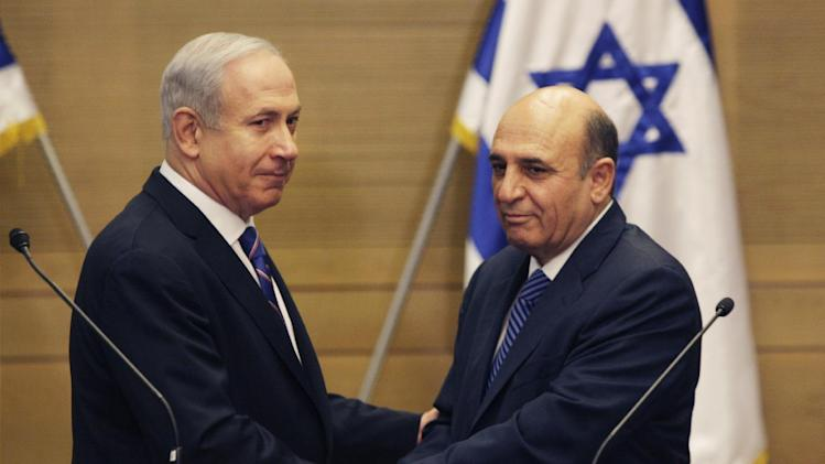 "Israel's Prime Minister Benjamin Netanyahu, left, and Kadima party leader Shaul Mofaz shake hands before holding a joint press conference announcing the new coalition government, in Jerusalem, Tuesday, May 8, 2012. Netanyahu said Tuesday his new coalition government will promote a ""responsible"" peace process with the Palestinians. (AP Photo/Sebastian Scheiner)"