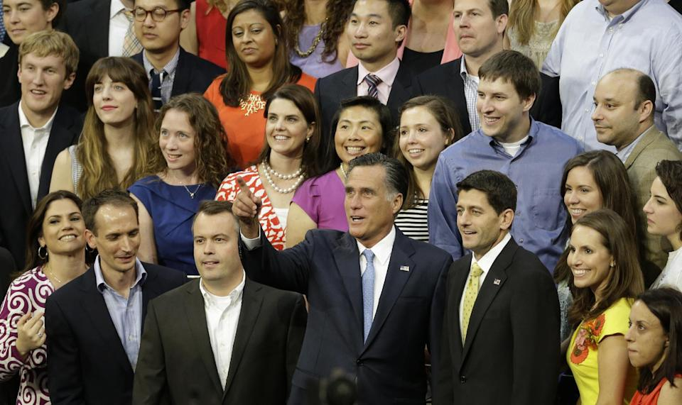 Republican presidential nominee Mitt Romney points to the photographer as he and vice presidential nominee, Rep. Paul Ryan, right, pose for a group photo with campaign staff before the Republican National Convention in Tampa, Fla., on Thursday, Aug. 30, 2012. (AP Photo/Lynne Sladky)