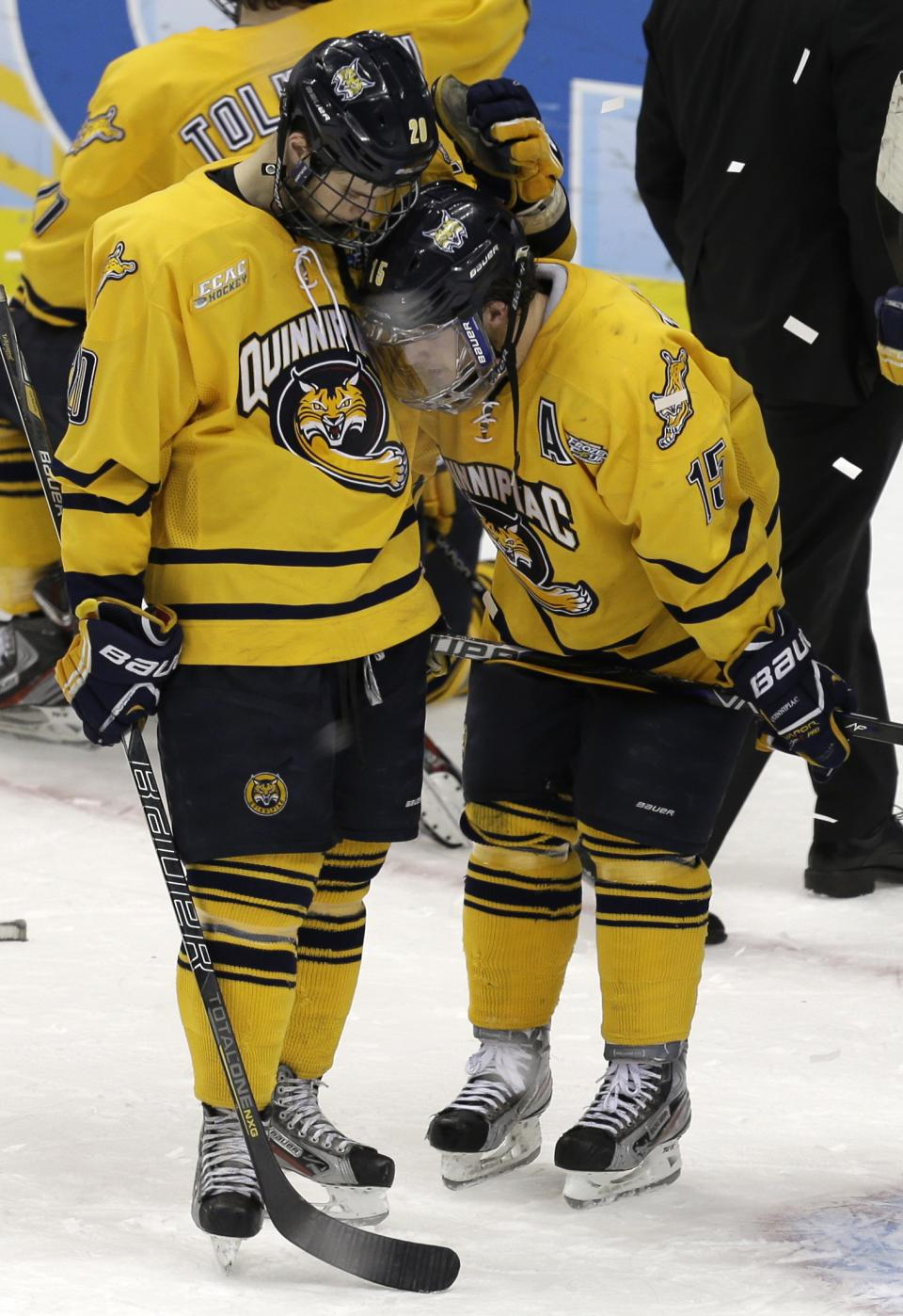 Quinnipiac's Matthew Peca, left, and Kellen Jones (15) console each other after losing to Yale 4-0 in the NCAA men's college hockey national championship game in Pittsburgh Saturday, April 13, 2013. (AP Photo/Gene Puskar)