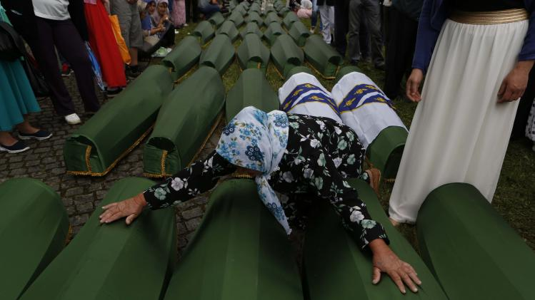 A Bosnian Muslim woman cries near the coffins bearing the remains of her relatives in Srebrenica, Bosnia, Friday, July 11, 2014. Thousands of people gathered at the Potocari Memorial Center for a memorial ceremony and funeral of 175 victims of Europe's worst massacre since World War II.
