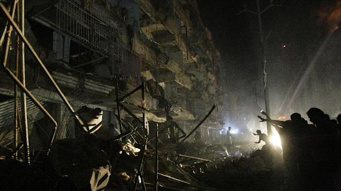 Pakistanis check the site of a bomb blast in Karachi, Pakistan, Sunday, March 3, 2013. Pakistani officials say a bomb blast has killed dozens of people in a neighborhood dominated by Shiite Muslims in the southern city of Karachi. (AP Photo/Fareed Khan)