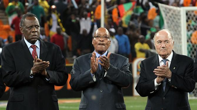 FILE - In this Feb. 10, 2013 file photo, Confederation of African Football (CAF)  President Issa Hayatou, left, South African President Jacob Zuma, center, and FIFA President Sepp Blatter applaud ahead of the African Cup of Nations final soccer match between Burkina Faso and Nigeria at Soccer City Stadium in Johannesburg, South Africa. The son of a sultan from northern Cameroon, Issa Hayatou has ruled African soccer for 27 years and counting, a decade longer than Sepp Blatter has been in charge of FIFA. (AP Photo/Themba Hadebe,File)
