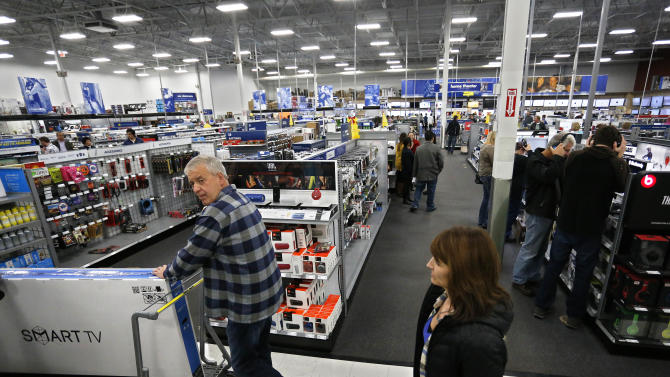 A man wheels a large television to the check out line during a Thanksgiving day sale at a Best Buy store in Broomfield, Colo., on Thursday, Nov. 27, 2014. (AP Photo/Brennan Linsley)