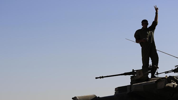 An Israeli soldier stands on top of a tank and makes the victory sign near the Israel Gaza border, Thursday, July 31, 2014. An Israeli defense official says the 16,000 additional reservists who are being called up will provide relief for troops who are currently fighting in Gaza. But Israeli officials have said they don't rule out expanding the Gaza operation in the coming days. (AP Photo/Tsafrir Abayov)