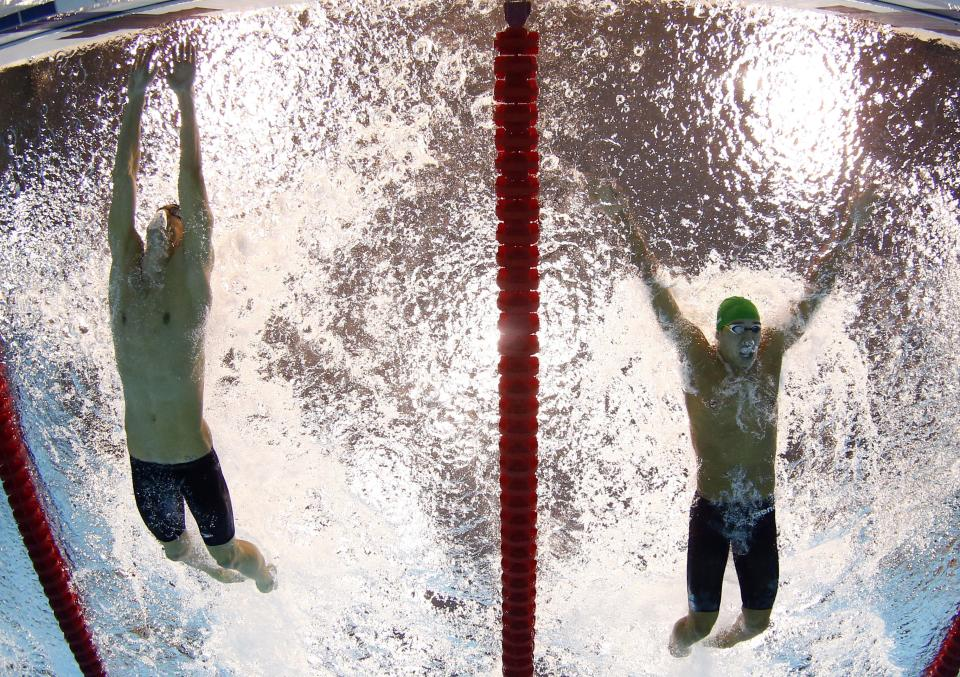 United States' Michael Phelps touches the wall as South Africa's Chad le Clos closes in for second place during the men's 100-meter butterfly final at the Aquatics Centre in the Olympic Park during the 2012 Summer Olympics in London, Friday, Aug. 3, 2012. (AP Photo/Mark J. Terrill)