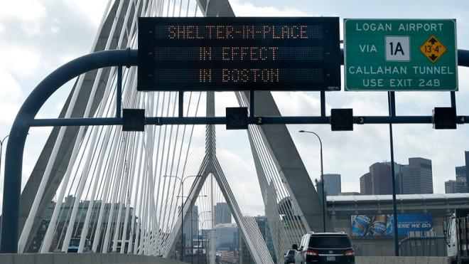 """A message calling for Boston citizens to """"Shelter in Place"""" flashes above I-93 on April 19."""