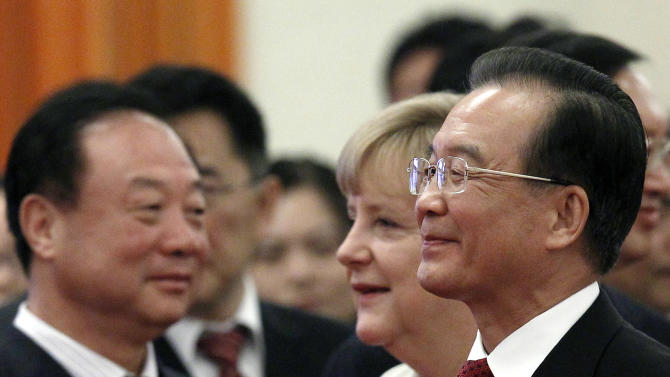 German Chancellor Angela Merkel, second from right, and Chinese Premier Wen Jiabao, right, walk past Chinese officials during a welcome ceremony held at the Great hall of the People in Beijing Thursday, Aug. 30, 2012. (AP Photo/Ng Han Guan)