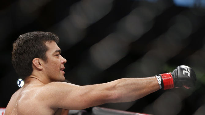 Lyoto Machida, from Brazil, celebrates after defeating CB Dollaway, from the United States, during their UFC middleweight mixed martial arts bout in Barueri, on the outskirts of Sao Paulo, Brazil, early Sunday, Dec. 21, 2014. (AP Photo/Andre Penner)