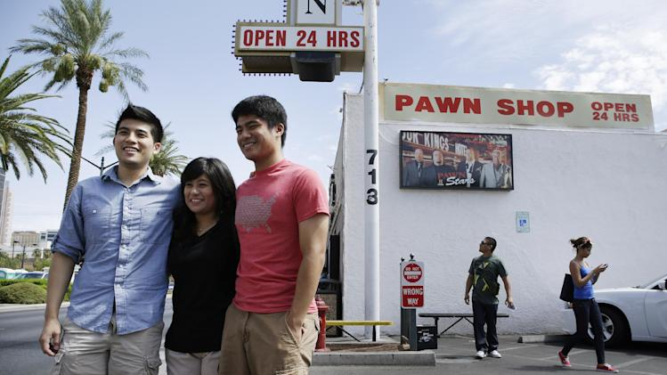 From left, Melvin Effendi, Caylin Effendi and Delwyn Effendi have their picture taken at the Gold & Silver Pawn Shop in Las Vegas Monday, July 28, 2014, in Las Vegas. Rick Harrison, owner of the pawn shop and one of the stars of the reality television series Pawn Stars, has proposed building a shopping plaza on land nearby. (AP Photo/John Locher)
