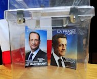 Declarations of faith from French 2012 presidential candidates, France's President and Union for a Popular Movement (UMP) candidate Nicolas Sarkozy (R) and France's Socialist Party (PS) candidate Francois Hollande, are put in an urn in front of a voting booth in Bethune, northern France