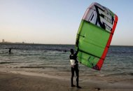 A Libyan man prepares to practice kitesurfing in Tripoli on December 8, 2012. Neon crescents twirl over the sheltered waters of Tripoli's main port, one of the hangouts of Libya's growing kitesurfing community, thriving after the ouster of dictator Moamer Kadhafi