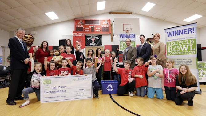 IMAGE DISTRIBUTED FOR KEEP AMERICA BEAUTIFUL - Keep America Beautiful president Matt McKenna, left, poses with children and dignitaries after presenting a check to Taylor Primary School as it was announced as the winner of the national Recyle-Bowl K-12 recycling competition in Kokomo, Ind.,Wednesday, Feb. 13, 2013. (AJ Mast /AP Images for Keep America Beautiful)