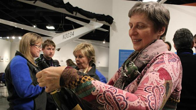 Irina Tiukhtyaev writes a congratulatory message to her husband, pilot Leonid Tiukhtyaev, on a champagne bottle during a celebration at the Two Eagles Balloon mission control in Albuquerque, N.M., on Saturday, Jan. 31, 2015. Leonid Tiukhtyaev and fellow pilot Troy Bradley successfully crossed the Pacific Ocean in their helium-filled balloon and surpassed two major distance and duration records. (AP Photos/Susan Montoya Bryan)