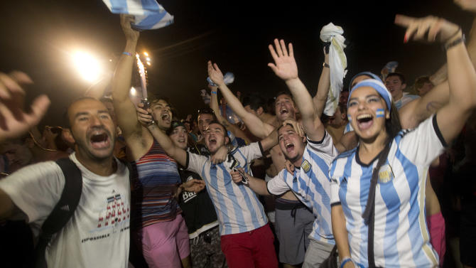 Soccer fans of the Argentina national soccer team celebrate their team's victory during a live broadcast of the soccer World Cup match between Argentina and the Netherlands, inside the FIFA Fan Fest area on Copacabana beach, in Rio de Janeiro, Brazil, Wednesday, July 9, 2014. Argentina made it to the World Cup final with a 4-2 shootout win over the Netherlands after the game finished in a 0-0 stalemate. (AP Photo/Silvia Izquierdo)