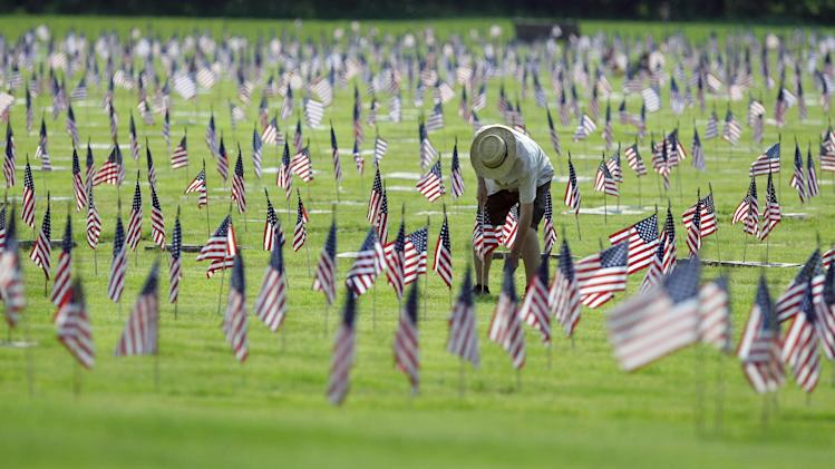 A man uprights a fallen flag at graves of military personnel and their families before Memorial Day ceremonies at Brig. General William C. Doyle Veterans Memorial Cemetery in Wrightstown N.J., Saturday, May 26,  2012. (AP Photo/Mel Evans)