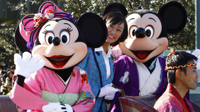 FILE - In this Jan. 1, 2010 file photo, Mickey Mouse and Minnie Mouse characters wave to visitors and guests during the annual Disney characters' procession at the Tokyo Disneyland in Urayasu, near Tokyo. Walt Disney Co. reports quarterly financial results Thursday, Nov. 10, 2011, after the market close. (AP Photo/Shizuo Kambayashi, File)