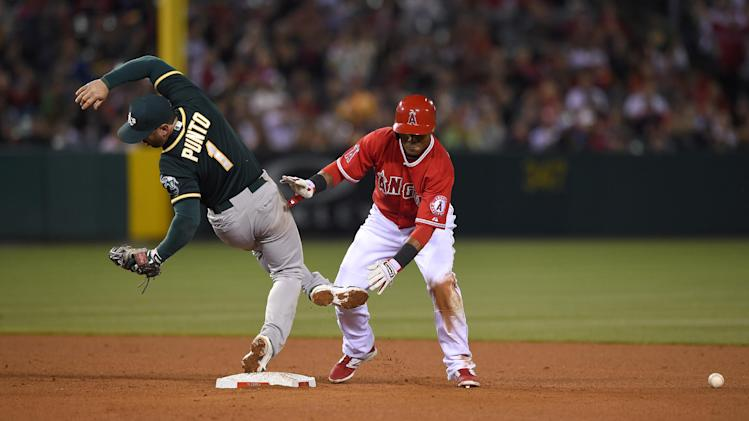 Oakland Athletics third baseman Nick Punto, left, falls after colliding with Los Angeles Angels' Erick Aybar as Aybar slid into second on a hit by J.B. Shuck during the seventh inning of a baseball game, Wednesday, April 16, 2014, in Anaheim, Calif. (AP Photo/Mark J. Terrill)