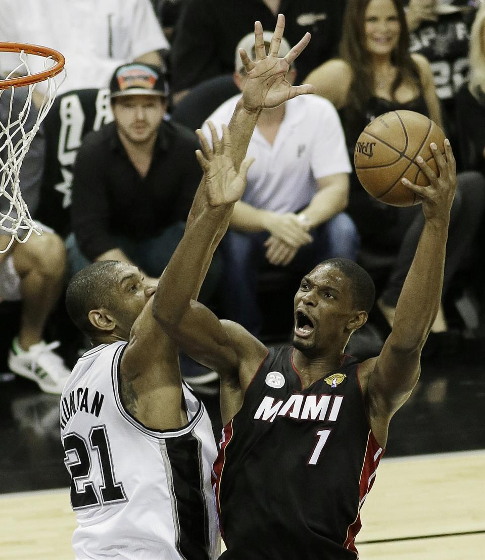 Miami Heat's Chris Bosh (1) scores against San Antonio Spurs' Tim Duncan (21) during the first half at Game 5 of the NBA Finals basketball series, Sunday, June 16, 2013, in San Antonio. (AP Photo/David J. Phillip)